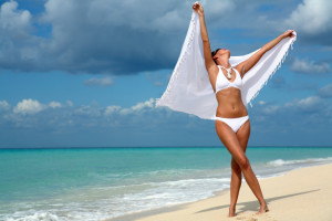 woman dancing on the beach with a white sarong